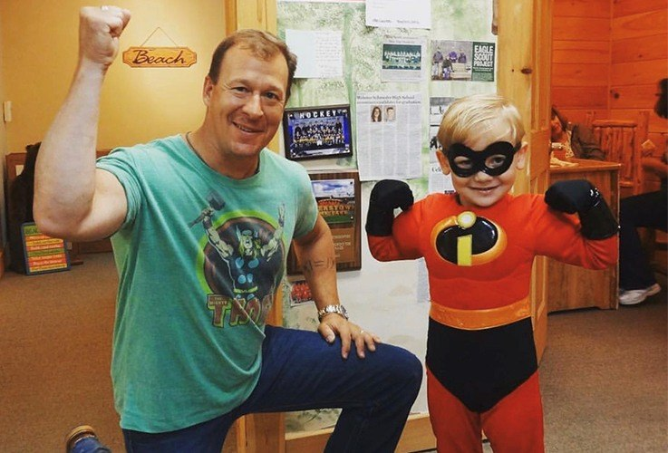 Dr. Drabik posing with a child in an Incredibles costume