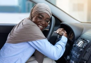 person with braces sitting in the driver's seat of their car going to visit their orthodontist in Rochester