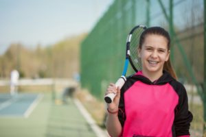 Girl playing tennis with braces