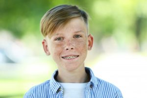 Boy in collared shirt with braces smiling after orthodontic treatment coverage