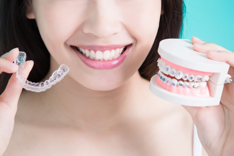 Smiling woman holding braces and Invisalign