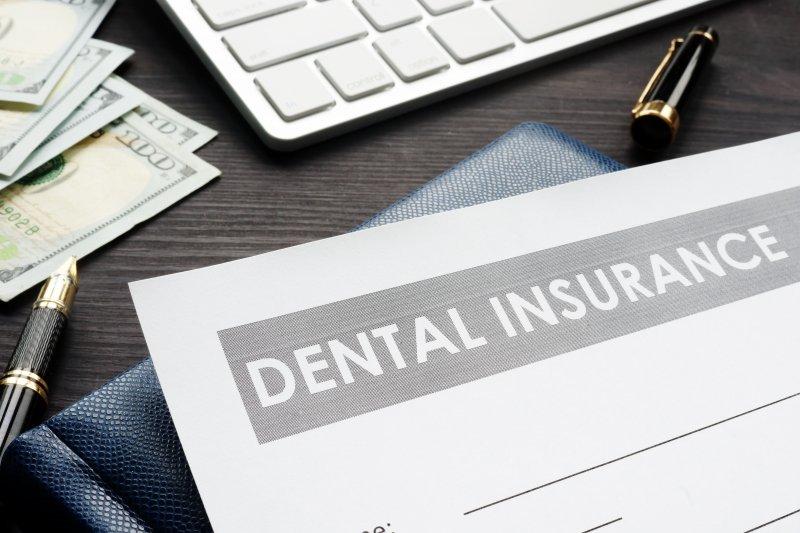 Dental insurance form on desktop with money
