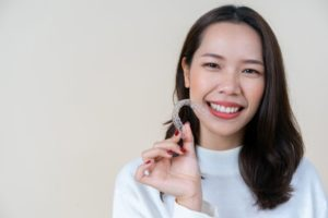 Woman smiling with Invisalign while looking at the camera