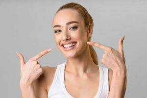 Woman pointing to her white teeth