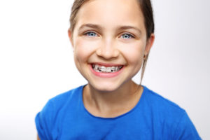 Young girl with braces smiling on white background